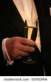 a man in a suit with a glass in hand