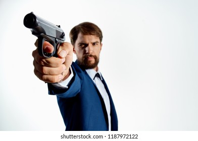 a man in a suit with a gun in his hands