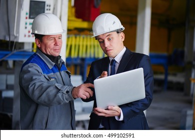 The man in the suit and the helmet holds the portable computer and shows up on the screen to the worker in overalls in an industrial building