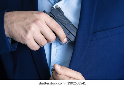 man in a suit hides a gun in his pocket