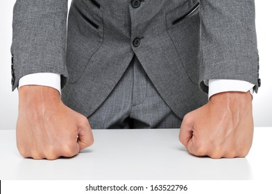 man in suit with his fists on the desk