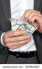 Man in suit hold american dollars in arm.
