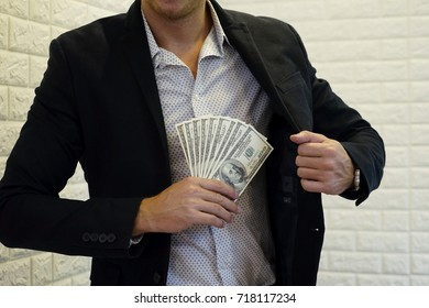 The man with suit holding the Bank note from his packet. The Corruption or Anti-corruption.