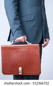 A man in a suit holding a brown briefcase