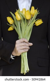 man in a suit holding bunch of yellow tulips