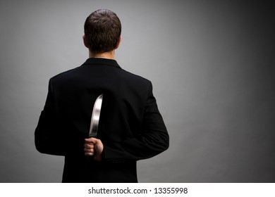 A man in suit holding knife behind back (light gray background version)