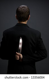 A man in suit holding knife behind back (dark gray background version, vertical close-up)