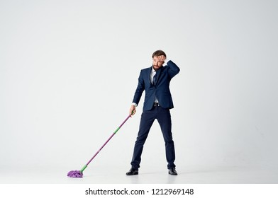 man in a suit holding a mop
