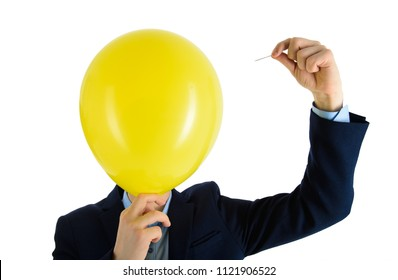 Man in suit holding needle over yellow air balloon, a moment before bubble burst. Isolated on white.