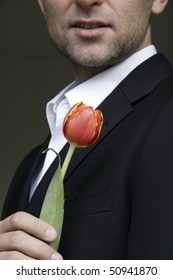 man in a suit holding one red tulip