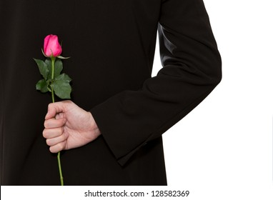 man in suit holding a pink rose in his back