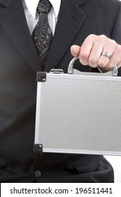 A man in a suit holding a silver briefcase.