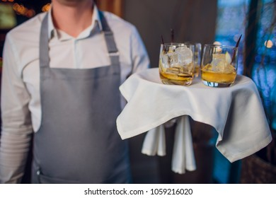 Man in suit holding silver tray with glasses of whiskey