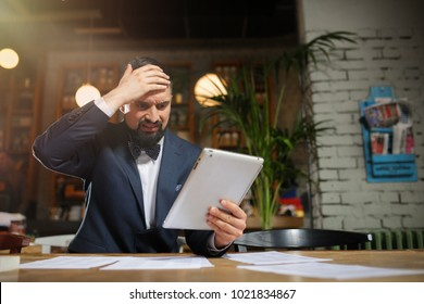 man in suit holding tablet disappointed