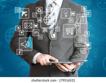 Man in suit holding tablet pc and application icons in hand. The concept of software