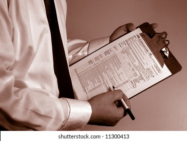 man in suit holding tax form
