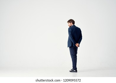man in suit holds hands behind his back