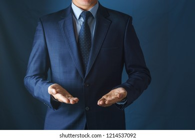 Man in suit holds hands with palms up.