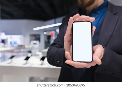 A man in a suit holds in his hands a modern smartphone with a white screen. A business man shows a trendy smartphone against the backdrop of an electronics store. The consultant offers a smartphone.