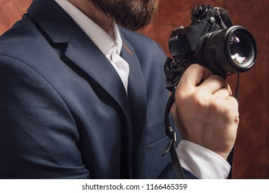 Man in suit holds old camera in hand