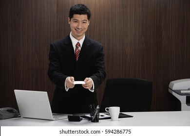 A man in a suit holds out his business card