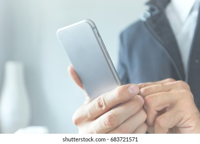 A man in a suit holds a phone in his hand