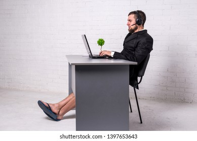 Man in a suit and home shorts holding a conference on a laptop computer. Concept of remote work, freelancing. Workaholic working on a day off.
