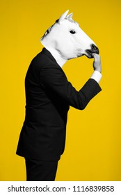 A man in a suit and a horse mask bites own hand. Conceptual business background