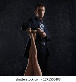 Man in suit leans on female legs raised up.
