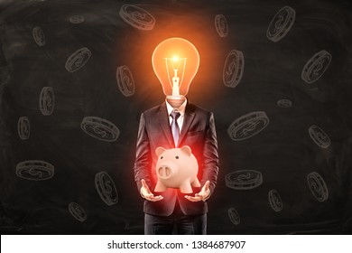 Man in suit with lightbulb instead head, levitating cute pink glaring piggy bank above palms, standing against black wall with coin pattern on it. Business ideas. Achieve success. Business acumen.