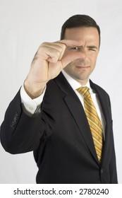 Man in suit looking through finger tips