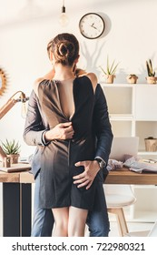 Man in a suit making out with woman and unzipping her dress