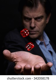 Man, in a suit no tie, holding red dices, taking a risk on a black background