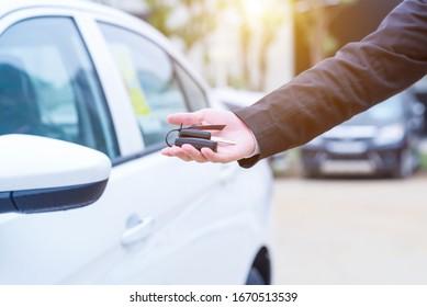 Mann im Anzug, der einen Autoschlüssel für den Beobachter anbietet, mit einem Auto im Ohr