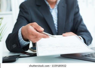 Man in a suit offers to sign a contract holding a pen and documents for signature