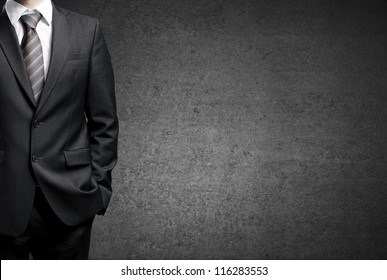 man in suit on a concrete wall background