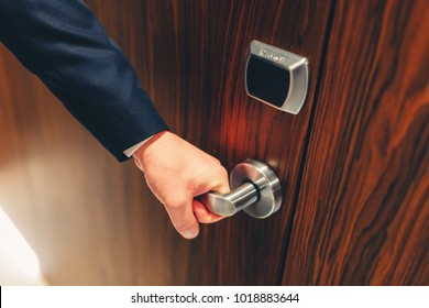 Man in a suit opens the door to the hotel room. The hotel door young man holding the handle in front of an electronic sensor door. Stylishly toned photo
