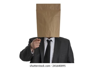 A Man in suit with a paper bag on his head pointing into the camera isolated on white background