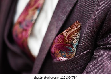 Man in suit, plaid texture, bow tie and pocket square, close up white background