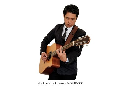 Man in suit playing guitar on white background.