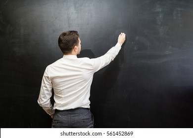 Man in suit pointing something on chalkboard,back view,isolated.Copyspace blank.Teacher writing on black board