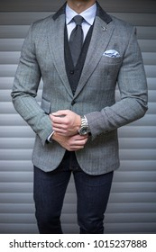 Man in suit posing and fixing his cufflinks
