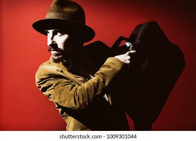 man in suit posing in studio with suitcase in hands