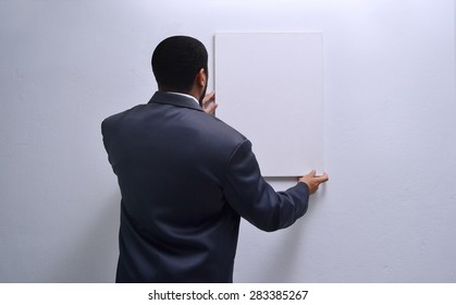 man in suit positioning chrome canvas on wall