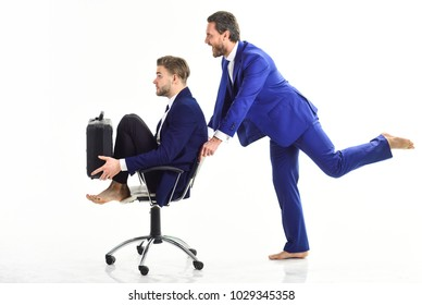 Man in suit pushing chair with colegue on. Two forcefully businessmen passing their working time in the office - isolated on white background.