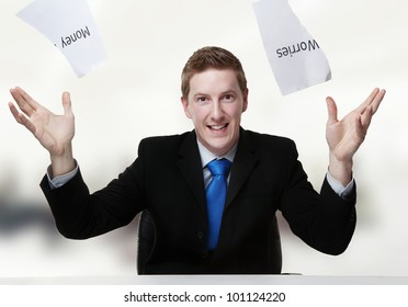 man in a suit sat at a desk just ripped up  a  piece of paper up with the words money worries printed on it and now throwing it away
