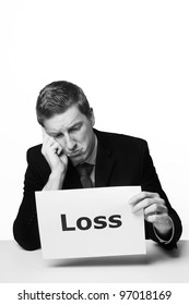 man in a suit sat at a desk look at a  piece of paper with the word loss printed on it