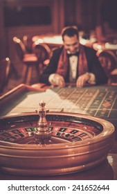 Man in suit and scarf playing roulette in a casino