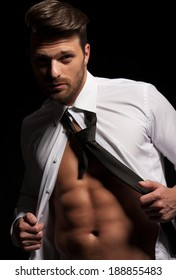 Man in suit showing abs a result of hard workout, muscular body, white shirt and tie
