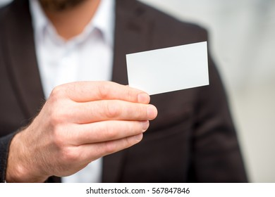 Man in the suit showing business card. Close-up view on the empty card to copy paste